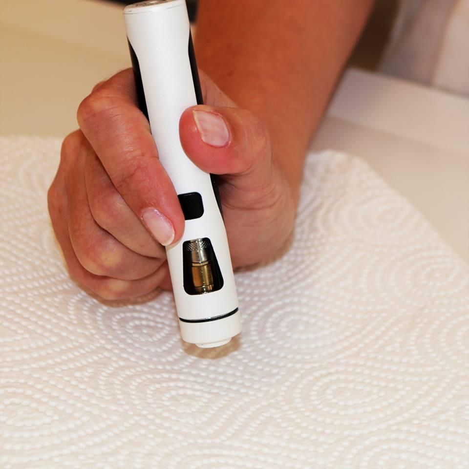 E-Zigarette wird über Küchenpapier ausgeklopft um Liquid aus Mundstück zu entfernen