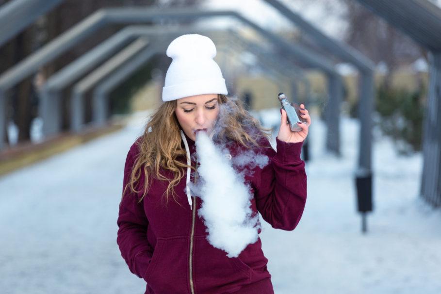 Dame mit E-Zigarette in Winter-Landschaft